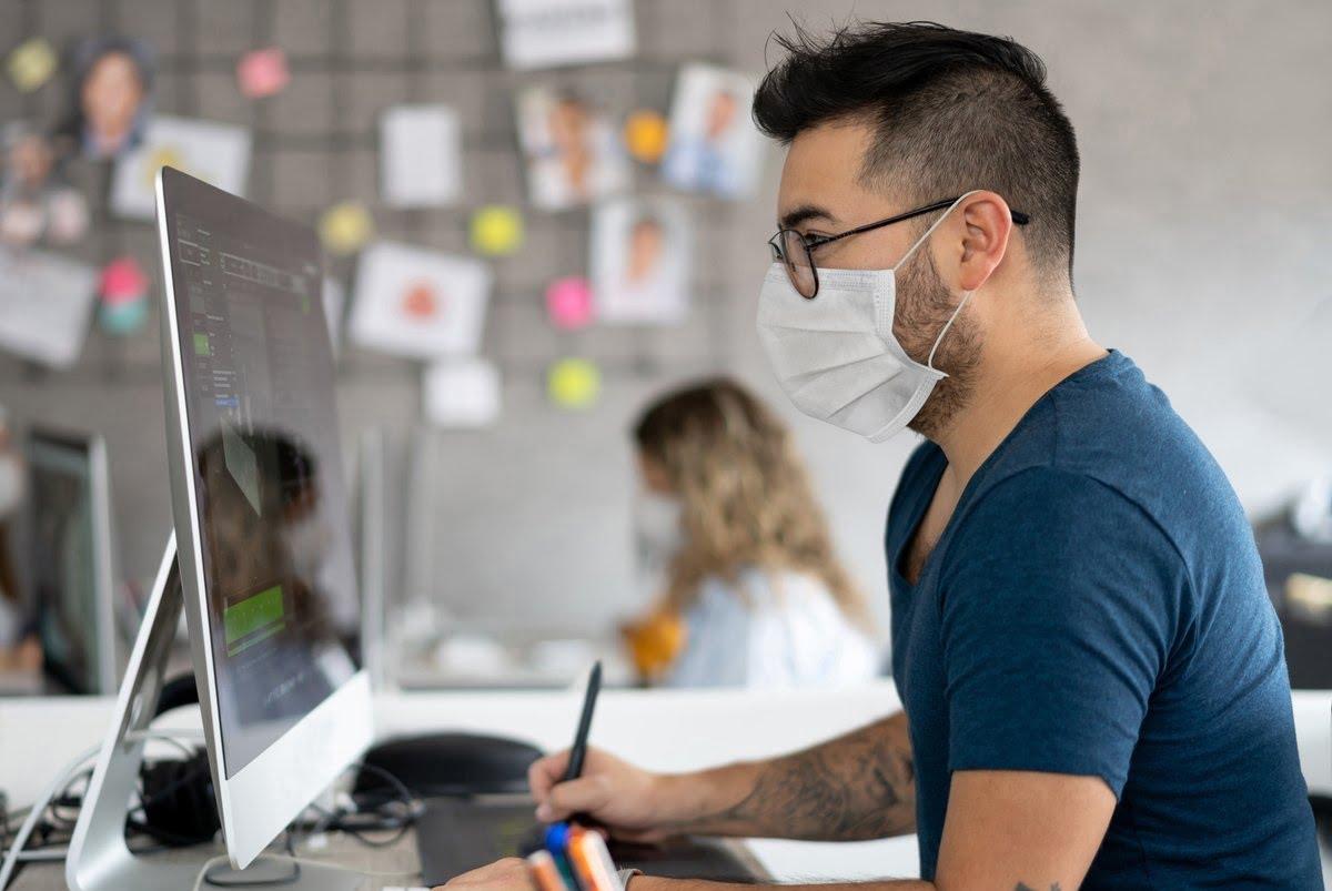 Angajat cu masca la birou